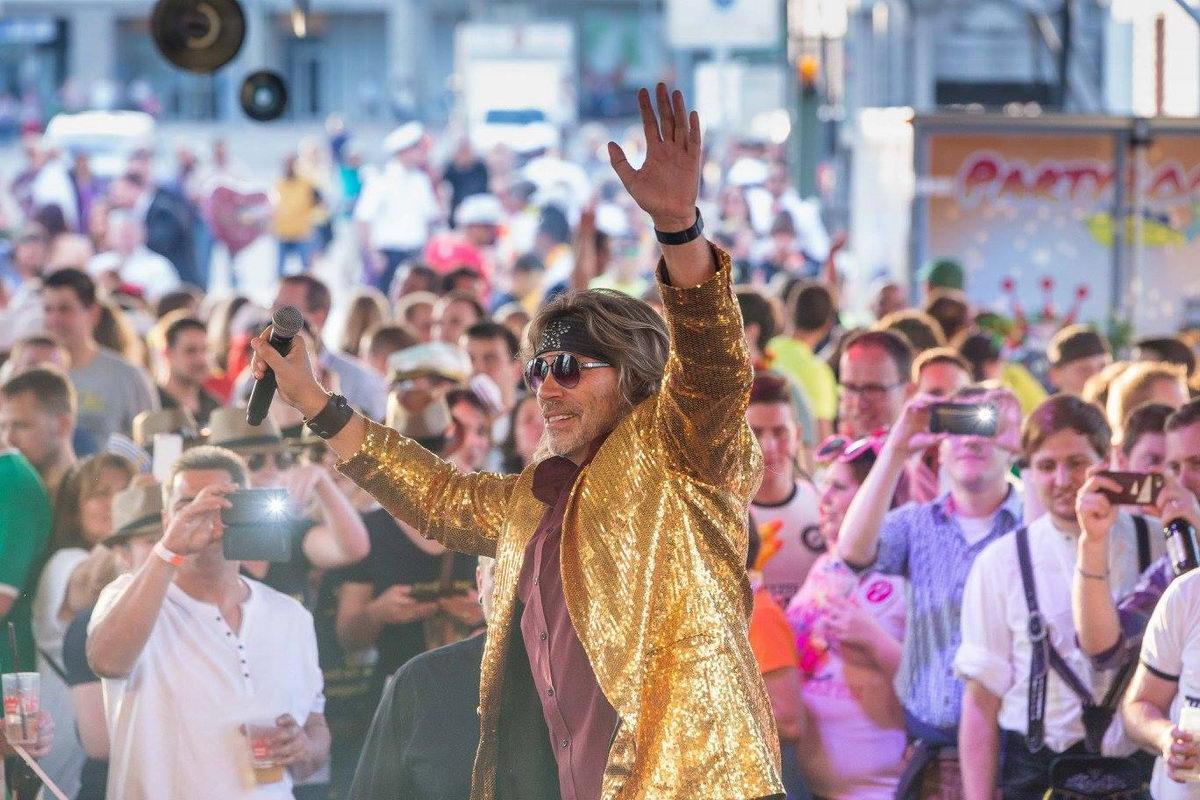 Sänger Boerney im goldenem Glitzerhemd hebt beide Arme hoch bei einem Stadtfest