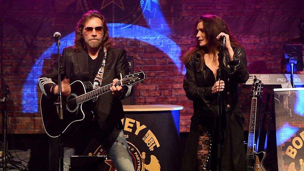 Sänger Boerney und Sängerin Jassy nebeneinander auf der Bühne Während einer Firmenfeier