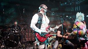 Gitarrist im Bühnenlicht. Im Hintergrund der Sänger und die Sängerin
